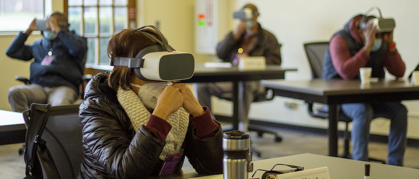 A woman wears a virtual reality headset and COVID face mask in a classroom at Western. Three students watch VR behind her.